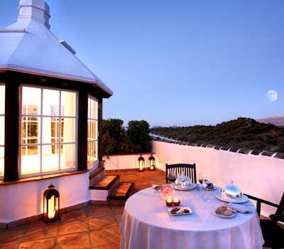 cena romanticas en azotea mesa servida para dos lamparas de fondo cielo y monte con arboles